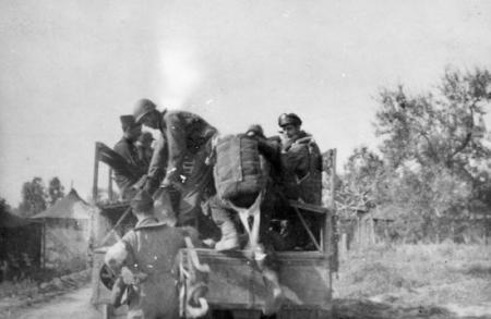 759 BS Crews being picked up from tent area by Army type 6 x 6 Truck 1944, Notice Officer`s Backpack Parashute--Gunners had front chutes