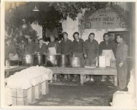 Christmas Day 1944. This is the cooks on the serving line, that's Mike Lograsso, Mess Sgt., making the funny face on the right side. Notice the Christmas tree and the way the ceiling was decorated with leaves and pine branches.